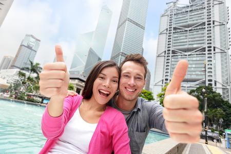 幸せの多民族・多文化の観光客カップル Hong Kong 市、アジア旅行の満足度に親指を表示します。カメラ - 旅行の人に笑顔とアジア系の若い白人の大人