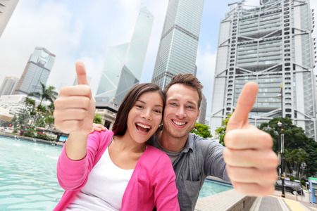 Happy multiethnic multicultural tourists couple showing thumbs up in satisfaction travelling in Hong Kong city, Asia. Young Asian and Caucasian adults smiling at camera - travel people