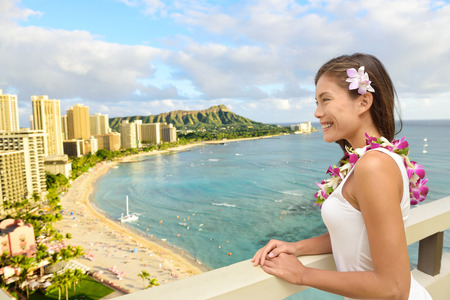 leis: Hawaii Travel - Asian tourist on Hawaiian holidays looking at Waikiki beach and Diamond Head in the background, Honolulu City, Oahu, USA from hotel room in luxury resort.