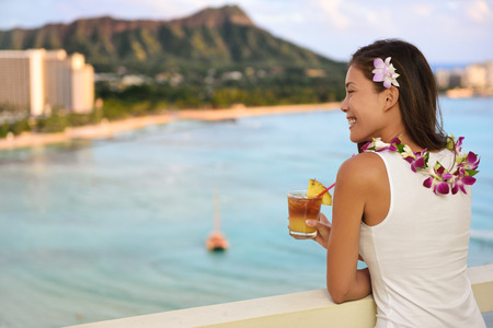 leis: Hawaiian woman drinking Mai Tai in resort on Waikiki beach, Hawaii. Beautiful Asian tourist on Hawaii travel looking at sunset over Diamond Head mountain in Honolulu, Oahu, Hawaii USA.