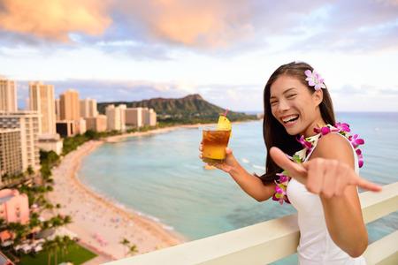 Hawaii vacation - Mai Tai and aloha spirit. Asian tourist woman showing Shaka hand sign as welcoming greeting and Hawaiian cocktail drink Mai Tai, during sunset overlooking Waikiki beach in Honolulu. Stock Photo