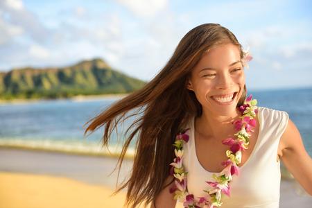 Hawaii beach woman happy on Hawaiian holidays. Portrait of cheerful young Asian adult laughing of fun during her travel summer vacation in Waikiki beach, Honolulu, Oahu, Hawaii, USA.