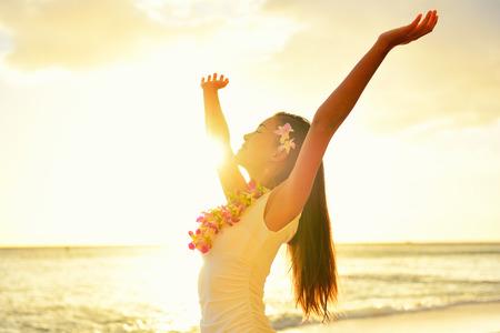happy young: Mujer despreocupada feliz libre en la playa de Hawai puesta de sol. Mujer hermosa en el resplandor del sol de oro de la puesta del sol con los brazos abiertos y el rostro levantado en el cielo disfrutando de la paz, la serenidad en la naturaleza.