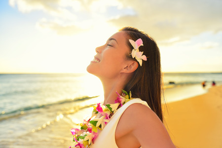 lei: Happy carefree woman free relaxing in Hawaii on hawaiian beach vacation. Beautiful woman in the golden sunshine glow of sunset breathing fresh air enjoying peace, serenity in nature.
