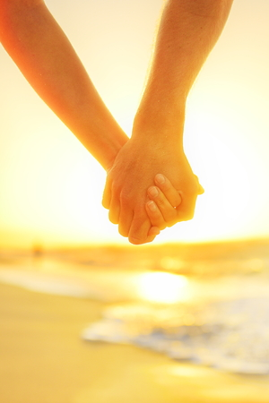 caribbeans: Couple in love holding hands - happy relationship. Closeup of male and female arms together at beach sunset during holidays tropical vacations.