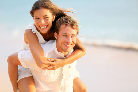 parejas felices: La pareja de amantes en el amor que data de la diversi�n en la playa retrato. Hermosa sana adultos j�venes novia que lleva a cuestas en novio abrazando feliz. Citas multirracial o el concepto de sana relaci�n. Foto de archivo