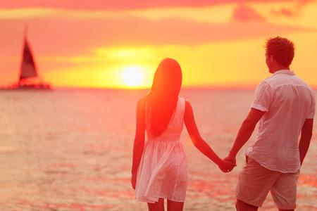 로맨스: 사랑은 해변 일몰에 손을 잡고 낭만적 인 신혼 부부. 여행 휴일 휴가 동안 바다 일몰을 즐기는 신혼 행복 한 젊은 커플. 인종 커플.