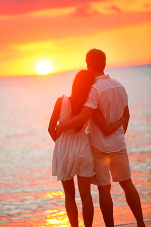 affectionate: Honeymoon couple romantic in love at beach sunset. Newlywed happy young couple hugging enjoying ocean sunset during travel holidays vacation getaway. Interracial couple, Asian woman, Caucasian man.