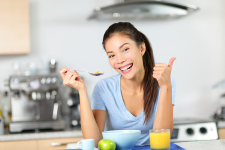 Woman eating breakfast cereals drinking orange juice smiling happy in the morning. Beautiful young multiracial woman sitting in her kitchen at home. Mixed race Asian Caucasian female model.