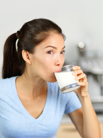 Almond milk woman drinking lactose-free beverage. Young Asian adult sipping a glass of organic soy based or nut milk drink as a dairy substitute for a vegan diet. Archivio Fotografico