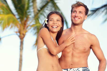Suntan fit body couple beach travel portrait. Handsome Caucasian man and good looking Asian woman fitness young adults with tanned skin for weight loss concept or beach vacation holidays.