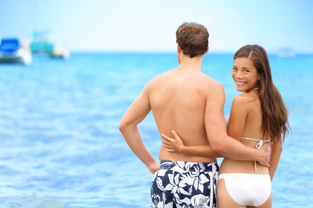 caribbeans: Couple beach portrait happy woman in relationship. Young Asian woman looking back at camera confident of her lover or having a secret to share, on tropical vacation. Stock Photo