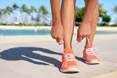 lacing sneakers: Sport fitness, Exercise running and lifestyle concept. Runner woman lacing running shoes trainers tying laces before jogging on a run. Fit healthy female feet and shoe close up. Stock Photo
