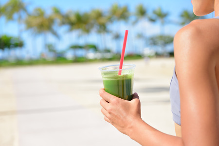 Vegetable green detox cleanse smoothie - Woman drinking after fitness running workout on summer day. Girl drinking green juice or smoothie in fitness and healthy lifestyle concept. Beautiful fit mixed race Asian Caucasian model outside on beach.
