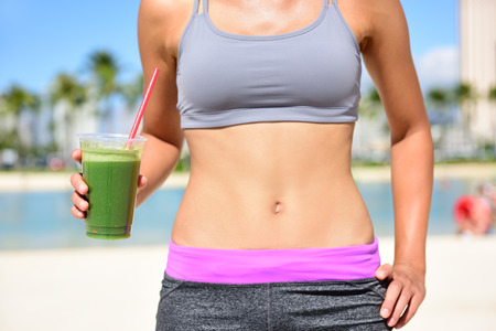 Healthy lifestyle fitness woman drinking green vegetable smoothie juice after running exercise.  Close up of smoothie and stomach. Healthy lifestyle concept with fit female model outside on beach.