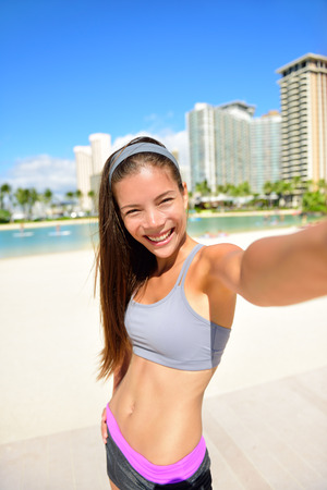 self   portrait: Fitness selfie woman self portrait after workout. Sport athlete taking selfies photo after working out running and training outdoors on beach. Fit female Asian Caucasian sport model smiling happy.