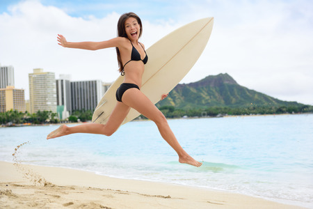 Surfing surfer happy having fun with surfboard jumping funny making excited face expression. Female bikini woman healthy active water sport lifestyle. Asian Caucasian model on Waikiki, Oahu, Hawaii. photo