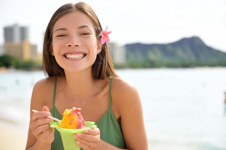 snow cone: Hawaii woman on Waikiki Beach eating Hawaiian shave ice, a local shaved ice dessert. Happy smiling mixed race Asian Caucasian female model enjoying traditional Hawaiian snack. Oahu, Hawaii, USA. Stock Photo