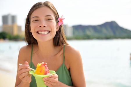 comiendo helado: Mujer Hawaii en la playa de Waikiki comer raspado de Hawai, un local de afeitado postre hielo. Feliz de raza mixta asi�tica modelo femenino de raza cauc�sica sonriente que goza del bocado tradicional hawaiana. Oahu, Hawaii, EE.UU..