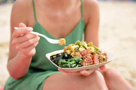 eating: Poke bowl salad plate. A traditional local Hawaii food dish with raw marinated ahi yellowfin tuna fish. Woman sitting on beach eating lunch. Stock Photo