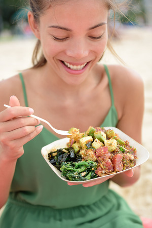 Woman eating local Hawaii food dish Poke bowl salad. Girl enjoying healthy lunch - a traditional local Hawaiian dish with raw marinated ahi yellowfin tuna fish. Healthy lifestyle concept.