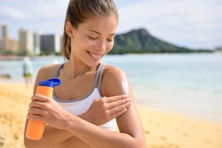 suntan lotion: Sunscreen fitness woman applying suntan lotion. Sporty Beautiful happy asian woman with suntan cream applying sun protection before fitness running on beach during summer. Waikiki, Oahu, Hawaii.