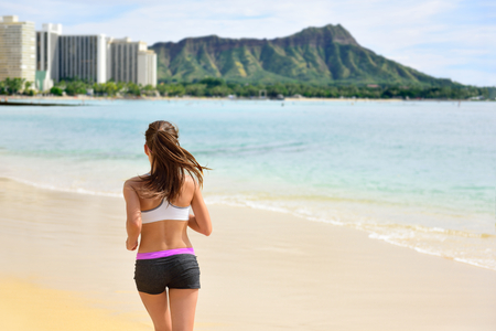 diamond head: Running woman runner jogging on beach run. Female athlete fitness runner jogger training living healthy active exercise lifestyle exercising outdoor on Waikiki Beach, Honolulu, Oahu, Hawaii, USA.