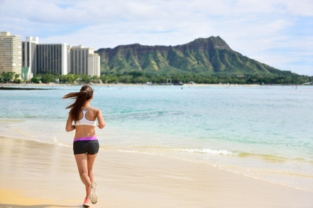 Female runner woman running jogging on beach run. Girl athlete fitness runner jogger training living healthy active exercise lifestyle exercising outdoor on Waikiki Beach, Honolulu, Oahu, Hawaii USA