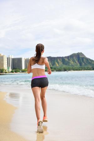 Running exercise - Female runner woman running and jogging on beach run. Athlete fitness runner jogger training living healthy active lifestyle exercising on Waikiki Beach, Honolulu, Oahu, Hawaii, USA photo