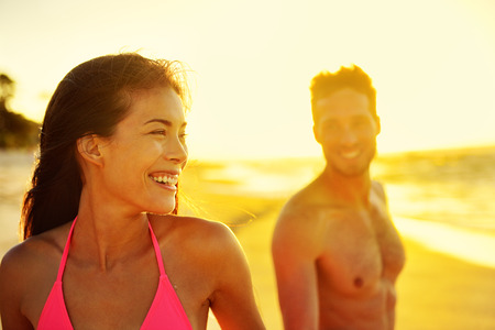 bikini couple: Happy multicultural couple on beach vacations. Hawaii holidays in sunset, young healthy adults together laughing walking in summer day. Asian mixed race woman, Caucasian man.