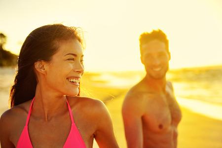 Pareja multicultural feliz en vacaciones en la playa. Vacaciones de Hawaii en la puesta del sol, jóvenes adultos sanos juntos riendo caminar en día de verano. Mujer asiática de raza mixta, hombre caucásico.