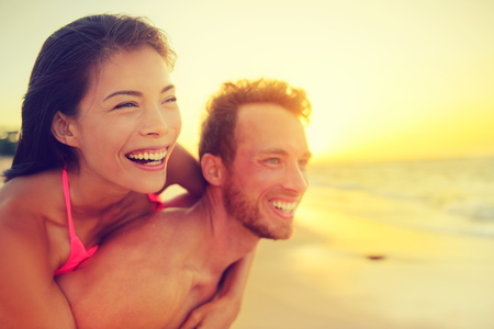 Happy beach fun multicultural couple - summer love in sunset. Young adults piggybacking playful and laughing on hawaiian beach, Asian woman and Caucasian man. Multiethnic mixed race relationship.
