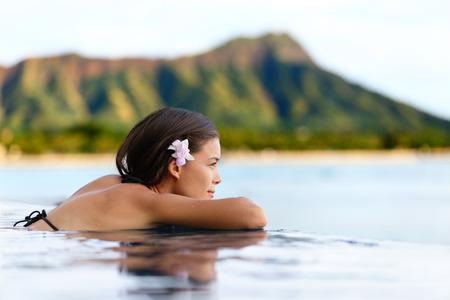 호놀룰루시, 오아후 섬, 하와이, 미국에 와이키키 해변이 내려다 보이는 일몰에서 휴식 수영장 리조트 여자. 여름 휴가를위한 웰빙과 휴식 개념.