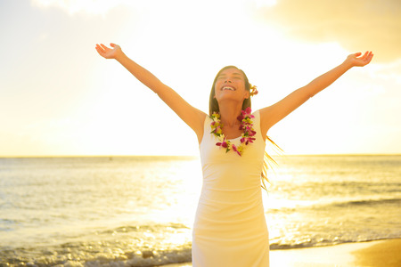 lei: Happy carefree woman free in Hawaii beach sunset. Beautiful woman in the golden sunshine glow of sunset with arms outspread and face raised in sky enjoying peace, serenity in nature. Stock Photo