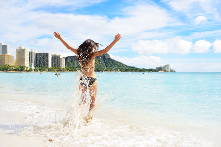 Waikiki beach fun - happy woman on Hawaii vacation. Unrecognizable young adult from behind jumping of joy in water waves, arms up with diamond head mountain in the background, landmark of Honolulu. Stock Photo