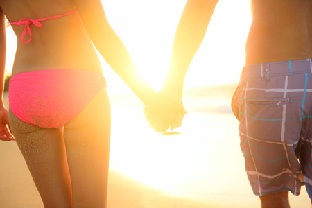 bikini couple: Holding hands couple in swimwear at beach. Rear view of fit couples buttocks and legs as weight loss concept at beach sunset during summer vacations.