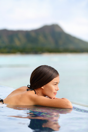 waikiki beach: Infinity pool spa hotel resort woman relaxing at sunset overlooking Waikiki beach in Honolulu city, Oahu island, Hawaii, USA. Wellness and relaxation concept for summer vacations. Stock Photo