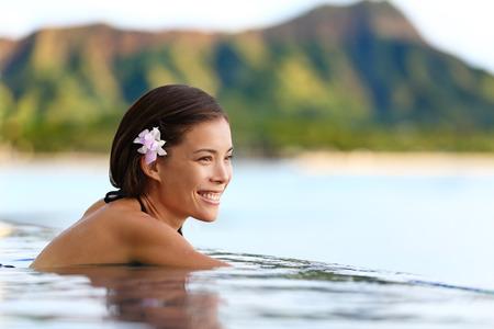 hawaii sunset: Swimming pool woman during beach travel holidays. Beautiful Asian woman tourist relaxing in infinity pool enjoying the view of Diamond Head mountain in Waikiki beach, Honolulu city, Oahu, Hawaii, USA. Stock Photo