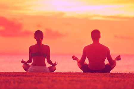 relaxed man: Meditation yoga couple meditating at serene beach sunset. Girl and man relaxing in lotus pose in calm zen moment in the ocean during yoga holiday class at resort retreat. Stock Photo