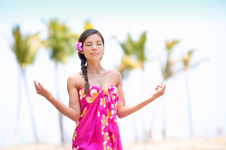 Happy Asian woman meditating on Hawaiian palm beach in sarong, hands up.  photo
