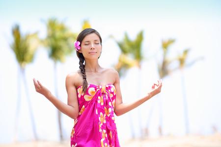 yoga beach: Happy Asian woman meditating on Hawaiian palm beach in sarong, hands up.  Stock Photo