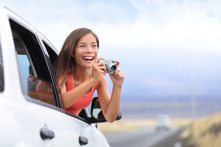 drivers: Woman tourist taking photo in car with camera driving on road trip travel vacation. Girl passenger taking picture out of window with vintage retro camera. Stock Photo