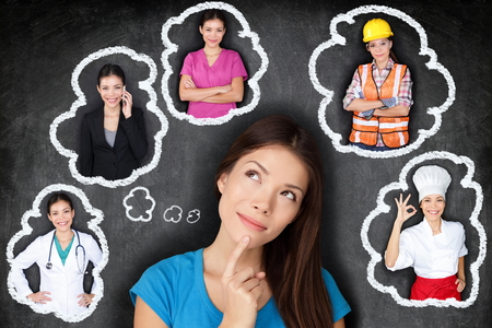 Education and career choice options - student thinking of future. Young Asian woman contemplating career options smiling looking up at thought bubbles on a blackboard with different professions