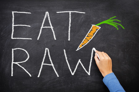 unprocessed: EAT RAW words written on blackboard - new trend in nutrition. The raw food diet consist of eating only uncooked, unprocessed generally vegetables and fruits, often in the form of smoothies and juices. Stock Photo