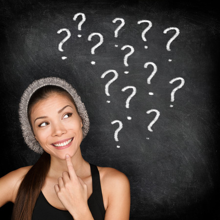 question concept: Student thinking with question marks on blackboard. Asian female young adult university or college student looking up at written drawings of question marks on chalkboard wondering career choices.