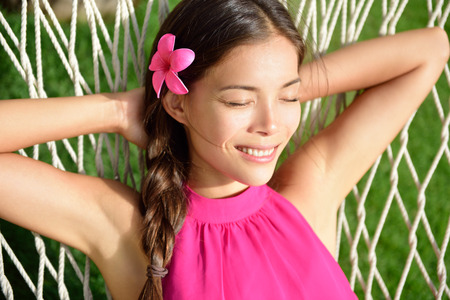 armpits: Sleeping woman relaxing on outdoor hammock in the sun tanning and having a nap in home garden or beach resort on summer holidays. Asian young adult portrait wearing pink hair flower and halter top.
