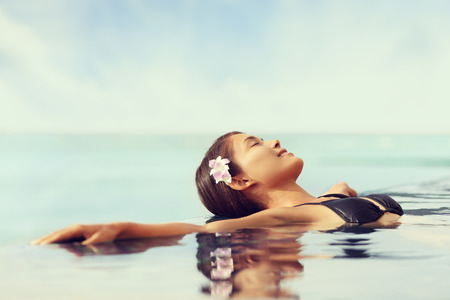 zen: Luxury resort woman relaxing in infinity swim pool. Asian young adult lying down in swimming pool of beach resort for summer holidays or travel vacations. Stock Photo