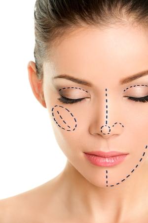 アジアの女性の顔に整形手術の線。肌化粧品医療処置のために鉛筆で目を閉じて女性の大人のクローズ アップ。目、鼻、頬、顎の外科的マーク行。