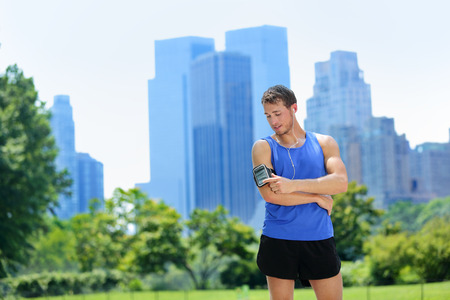 manhattans: New York City man runner listening music on smartphone. Male adult jogger running using touchscreen on armband for workout in Central Park with urban background of Manhattans skyscrapers skyline.