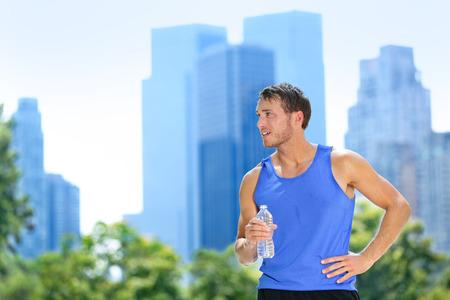 beber agua: Hombre del deporte beber botella de agua en la ciudad de Nueva York. Corredor masculino sudoroso y sediento después de correr en Central Park, Nueva York, Manhattan, con edificios urbanos horizonte en el fondo.